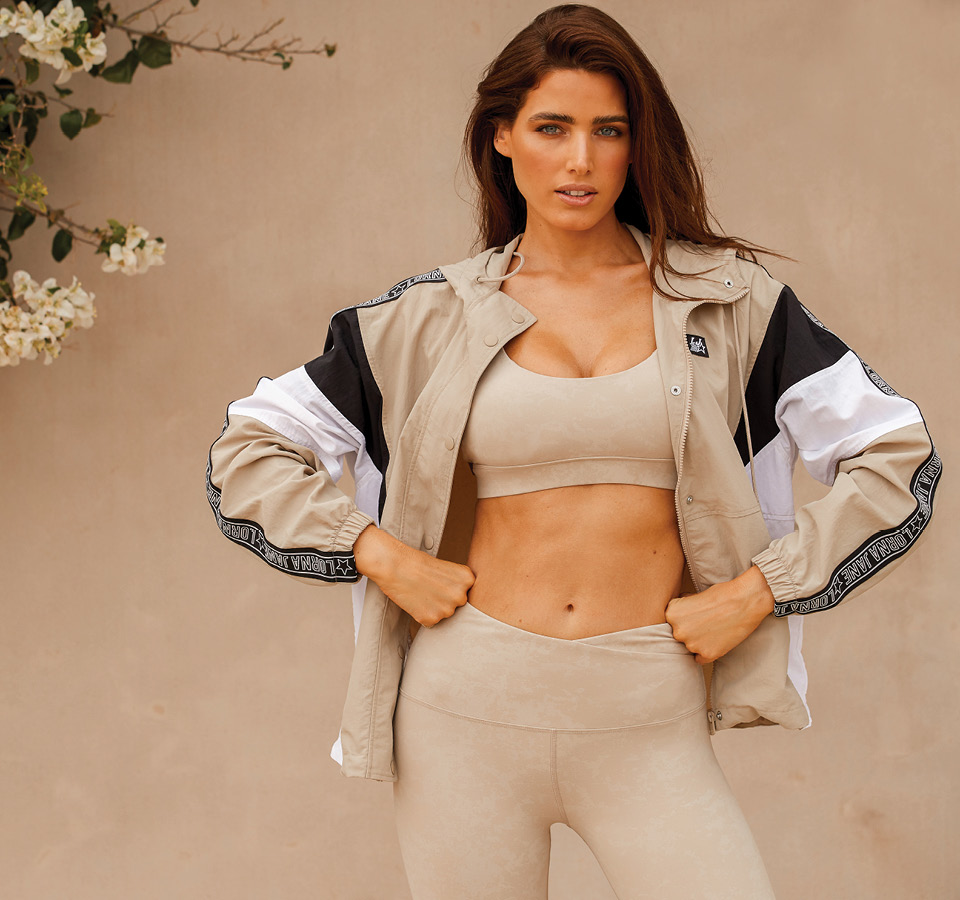 Decorative image of model in off white Lorna Jane jacket, sports bra and leggings